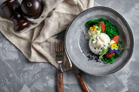 Burrata salad with strawberries and seaweed, on a gray background. Salad with buratta cheese on a gray plate and concrete marble background 版權商用圖片