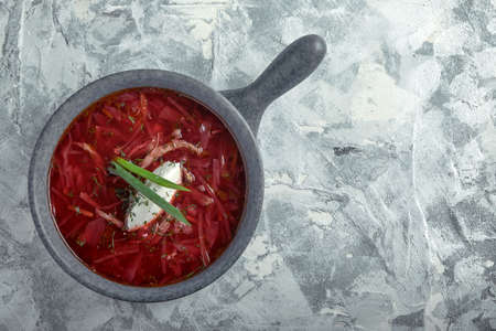Traditional Ukrainian Russian borsch with sour cream on a bowl. A plate of red beetroot soup borsch on a gray marble background. Traditional Ukrainian cuisine