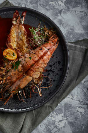 Grilled king prawns, with tomato sauce on a gray background, low key. Series concrete background. Food concept, food style, Copy space, food advertising for magazines and social networks.