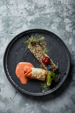 Black cod steak with tomato sauce and buckwheat popcorn, top view on a plate. Copy space, gray background.