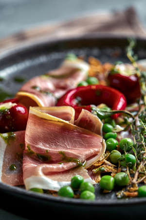 Italian prosciutto crudo and jamon with rosemary. Raw ham on a concrete gray background. Close-up Stockfoto