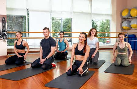 Gelukkig multiraciale groep jonge, lachende mooie meisjes en ruiten in sportkleding, yoga-oefeningen doen in de lotuspositie. Yogales of fitness. Groepsfitnessconcept, groepstrainingen, motivatie.