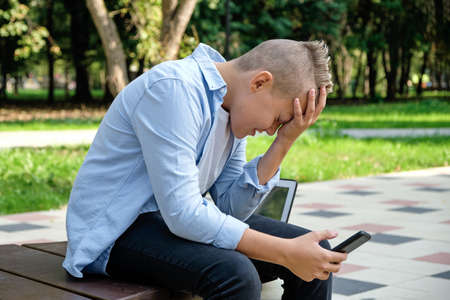 Problems of modern children. Young guy in the park with the phone upset. Depression is a mental disorder due to social networks. Online life, depression due to social development. Stock Photo