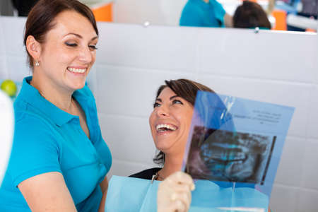 Close up female dentist pointing at patients X-ray image in dental office.