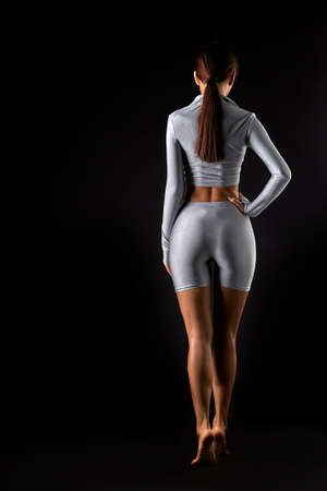 Rear view of female body with sexy ass on black background
