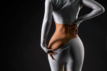 Rear view of female hands taking off pants showing sexy ass Stockfoto