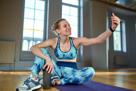 Chatting with friend. Beautiful young woman in sports clothing using her smart phone, makes selfie while doing yoga at gym
