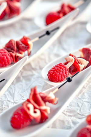 Delicious canapes hamon with raspberries. Concept of food, restaurant, catering, menu. Stock Photo