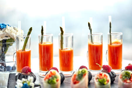 Set of cocktails made of carrot juice and asparagus. Healthy eating a snapshot of several carrots and asparagus standing on a table Фото со стока