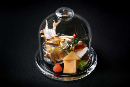 Assorted cheeses with berries and marmalade, mini serve in a glass flask. Fusion food concept, low key, copy space. Banco de Imagens