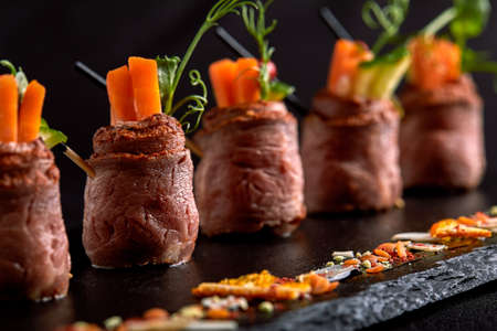 Mini roast beef rolls with vegetables, on a black slate plate, on a black background. Fusion food concept, low key, copy space