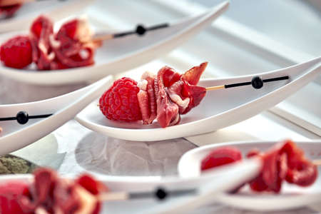 Delicious canapes hamon with raspberries. Concept of food, restaurant, catering, menu