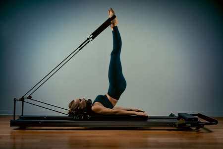 Young girl doing pilates exercises with a reformer bed. Beautiful slim fitness trainer on a reformer gray background, low key, art light, copy space advertising banner. Standard-Bild
