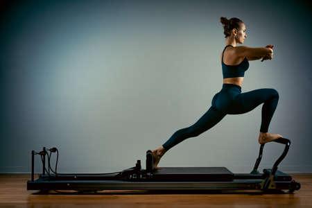 Junges Mädchen, das Pilates-Übungen mit einem Reformerbett macht. Schöner schlanker Fitnesstrainer auf reformergrauem Hintergrund, zurückhaltend, Kunstlicht, Werbebanner für Kopienraum Standard-Bild
