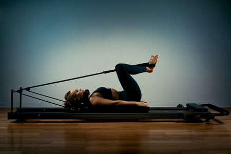 Young girl doing pilates exercises with a reformer bed. Beautiful slim fitness trainer on a reformer gray background, low key, art light, copy space advertising banner. Stock Photo