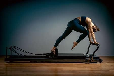 Junges Mädchen, das Pilates-Übungen mit einem Reformerbett macht. Schöner schlanker Fitnesstrainer auf reformergrauem Hintergrund, zurückhaltend, Kunstlicht, Werbebanner für Kopienraum