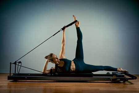 Young girl doing pilates exercises with a reformer bed. Beautiful slim fitness trainer on reformer gray background, low key, art light. Fitness concept Stok Fotoğraf