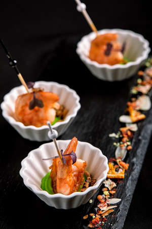 Canapes with tiger prawns on a skewer on a black background. The concept of catering food. Stock fotó