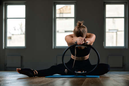 Young, beautiful, athletic girl is doing exercises with the Pilates ring in the gym on a gray background. Sporting Slavic girl in a blue, green suit. Copy space, gray background, sport banner for advertising. Banco de Imagens