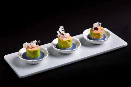 Baked salmon canapes with sauce, in white small saucers, concept catering food.