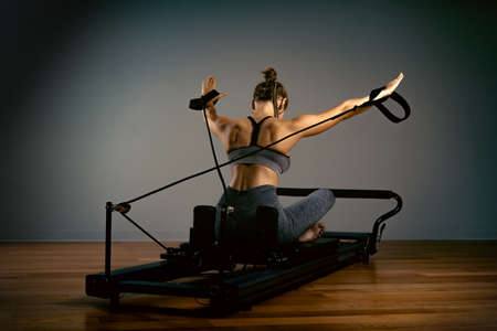 Young girl doing pilates exercises with a reformer bed. Beautiful slim fitness trainer on reformer gray background, low key, art light. Fitness concept 免版税图像