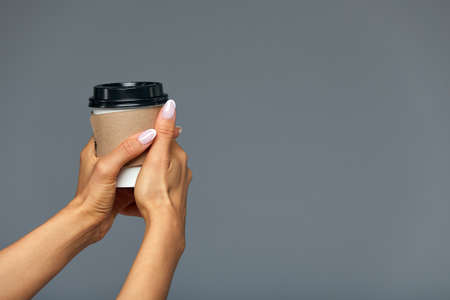 A female hand holds a white paper coffee cup with a black plastic cover on a grey background. Stock fotó