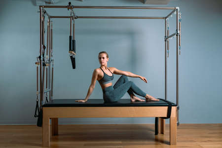 Pilates woman in a Cadillac reformer doing stretching exercises in the gym.