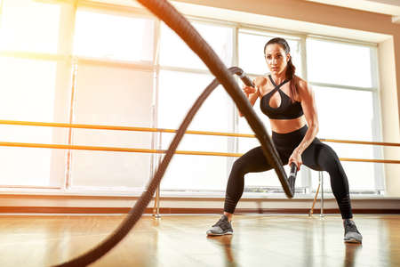Sportswoman working out with battle ropes at gym