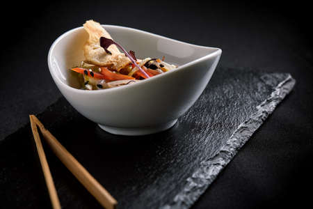 Asian with miso pasta, soy sauce, herbs. On a black stone table, with chopsticks. Copy top view Imagens