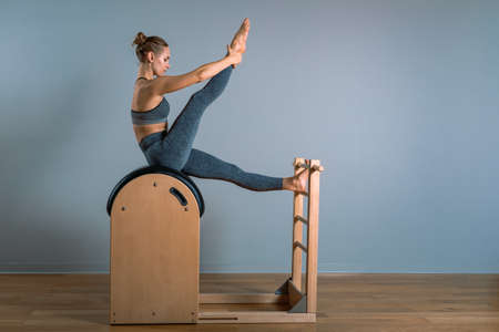 Beautiful positive blond woman is being prepared performing pilates exercise, training on barrel equipment. Fitness concept, special fitness equipment, healthy lifestyle, plastic. Copy space, sport banner for advertising.