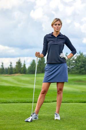 Portret van een mooie vrouw golfen op een groen veld buiten achtergrond. Het concept van golf, het streven naar uitmuntendheid, persoonlijke uitmuntendheid, koninklijke sport.