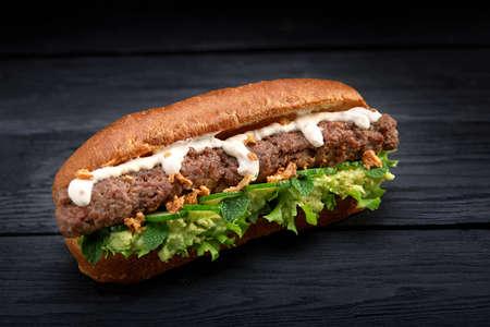 Nahaufnahme von Kebab-Sandwich auf schwarzem Holzhintergrund