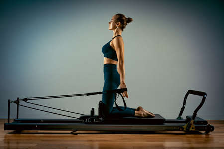 Young girl doing pilates exercises with a reformer bed. Beautiful slim fitness trainer on reformer gray background, low key, art light. Fitness concept Stock Photo