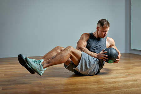 Strong man doing exercise with med ball. Photo of man perfect physique on grey background. Strength and motivation. Reklamní fotografie