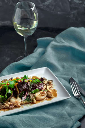 Salad of squid, mushrooms, and vegetables with a glass of wine. The view from the top. Copy-space