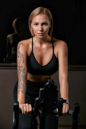 Young confident woman athlete exercising on bicycle indoors. Attractive determined fitness girl doing cycling exercises in dark gym. Functional workout training of sports girl. Cardio training Banco de Imagens