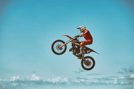 Extreme sports, motorcycle jumping. Motorcyclist makes an extreme jump against the sky. Film grain effect, illumination.