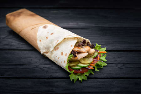 Shawarma rolled in lavash, moist grilled meat with onion, herbs and vegetables on wooden black background.