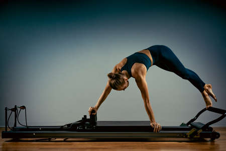 Young girl doing pilates exercises with a reformer bed. Beautiful slim fitness trainer on reformer gray background, low key, art light. Fitness concept.