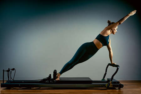 Young girl doing pilates exercises with a reformer bed. Beautiful slim fitness trainer on reformer gray background, low key, art light. Fitness concept