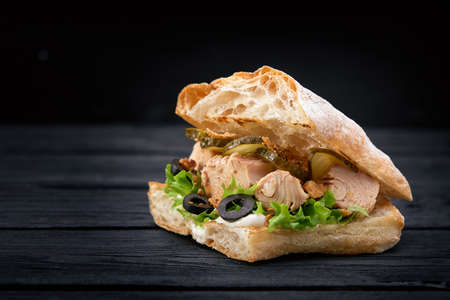American fast food. Juicy tuna sandwich with cheese, salad and olives on a dark background. Club food.