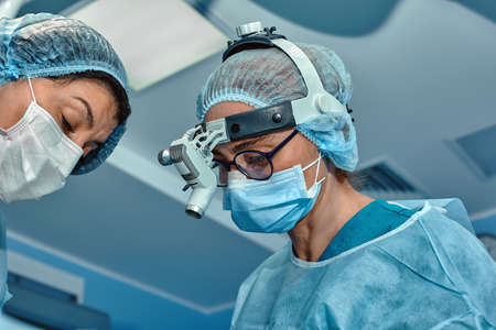 Two surgeons in protective uniform during the operation, on background of surgical room. Point of view shot