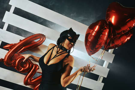 Sexy woman with large breasts wearing a black mask Easter bunny standing on a black background holding heart-shaped balloons and a love sign and looks very sensually