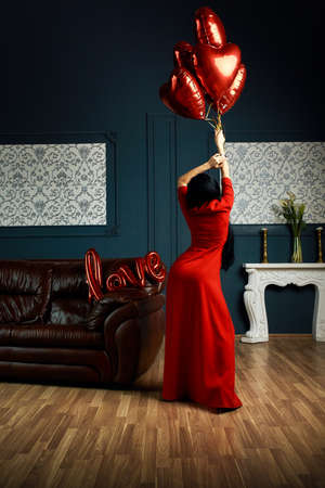 Sexy woman wearing in red dress standing near sofa and holding heart-shaped balloons and a love sign and looks very sensually Standard-Bild