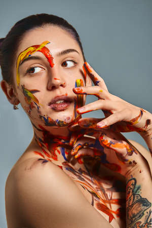Portrait of a beautiful girl in the paint. Closeup portrait of a girl with face and hands with different paint. Fashion art concept, beauty, creative people freelance people