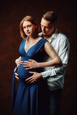 Pregnant couple posing for the camera on a brown background, low key. Fashion Pregnancy Concept. Copy space, brown background. 스톡 콘텐츠
