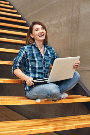 Happy freelancer girl working on laptop at the house forester. Work as a freelancer, free crapher, dream job, own business 스톡 콘텐츠