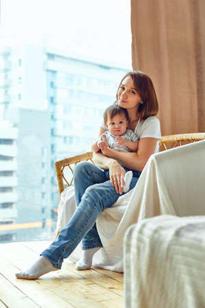 A woman with a child sitting on a chair by the window. happy mom, mom and baby. Copy space 스톡 콘텐츠
