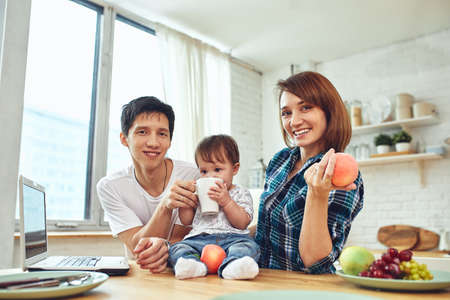 Happy international family concept. Dad, mom, son and little daughter posing for a camera at home, are engaged in home parenting. Home holidays, parenting, concept children and parents. 스톡 콘텐츠