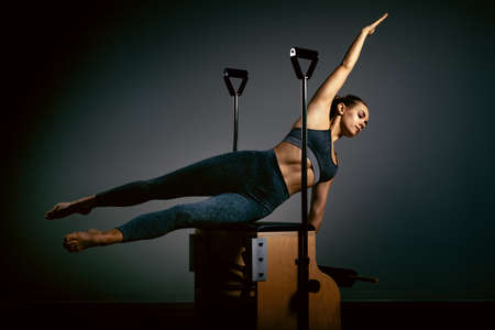 Young girl doing pilates exercises with a reformer bed. Beautiful slim fitness trainer on reformer gray background, low key, art light. Fitness concept 스톡 콘텐츠